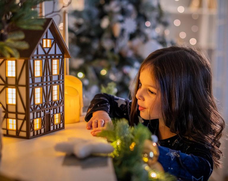 Домик-светильник создан из дерева и в стиле «Фахверк» на фоне рождественской елки